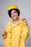 Skyddar bärande guling för kvinnabyggmästaren hjälmen och det total- hållande mätningsbandet Royaltyfri Fotografi