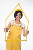 Skyddar bärande guling för kvinnabyggmästaren hjälmen och total- visning en husram Royaltyfri Foto
