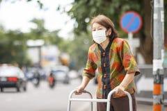 Skyddar den bärande maskeringen för den äldre kinesiska kvinnan för luftförorening Arkivbild