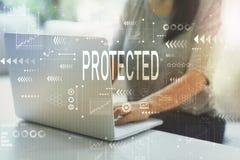 Skyddat med kvinnan som använder bärbara datorn arkivbild