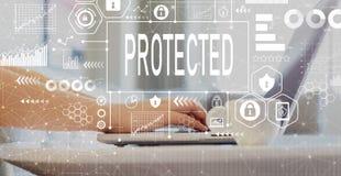 Skyddat med kvinnan som använder en bärbar dator arkivbild