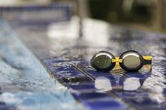Skyddsglasögon på sidan av en simbassäng Arkivbild