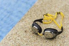 Skyddsglasögon på sidan av en simbassäng Arkivfoton
