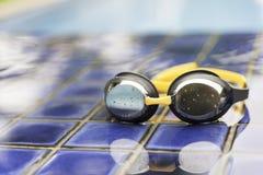 Skyddsglasögon på sidan av en simbassäng Fotografering för Bildbyråer