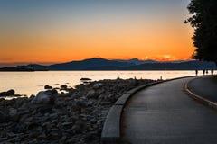 Skyddsmur mot havet och en fjärd med berg på horisont på solnedgången royaltyfria foton