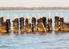 Skyddsmurar mot havet och förstärkningar med det gamla hjulet Royaltyfri Foto