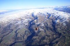 Skydive au-dessus de montagne de neige Photographie stock