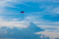 Skydiver ζωηρόχρωμο στο μπλε ουρανό πέρα από τη θάλασσα Στοκ Φωτογραφίες
