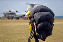 Skydiver carries a parachute after landing Stock Photos