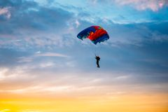 Skydiver On Colorful Parachute In Sunny Sky. Skydiver On Colorful Parachute In Sunny Sunset Sunrise Sky. Active Hobbies Stock Image