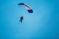 Skydiver en el paracaídas colorido en Sunny Sky Imagen de archivo libre de regalías