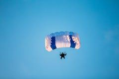 Skydiver en el paracaídas colorido en Sunny Sky Foto de archivo