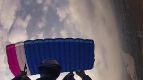 Skydiver en mosca del casco en el paracaídas en cielo nublado altura Deporte extremo velocidad metrajes