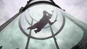 Skydiver för ung kvinna för utbildningsflyg i en vindtunnel Inomhus hoppa med fritt fall tunnelen lager videofilmer