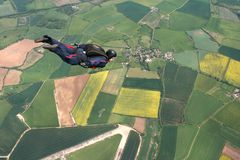 Skydiver flies past cameraman. Towards the direction of the dropzone Royalty Free Stock Photo