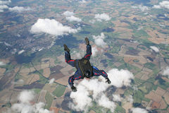Skydiver in freefall. With clouds beneath him Stock Photo