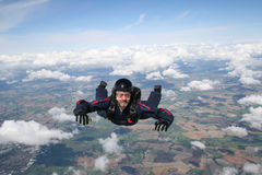 Skydiver in freefall. With clouds beneath him Stock Photos