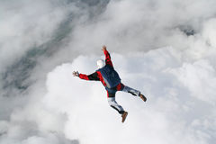 Skydiver in freefall. With clouds beneath him Stock Photography