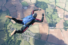 Skydiver in freefall high up in the air. On a sunny day Royalty Free Stock Images