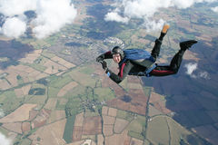 Skydiver in freefall high up in the air. On a sunny day Stock Photo