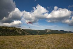Skydiver hovers over plateau royalty free stock photo