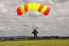 Skydiver landing. Parachute landing on dropzone bright canopy with skydiver Royalty Free Stock Photo