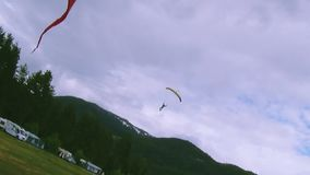 Skydiver landing on green field among forest, mountains. Yellow parachute. Extreme stunt. Adventure stock video