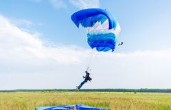 Parachutist landing on a green meadow after good flight. royalty free stock photography