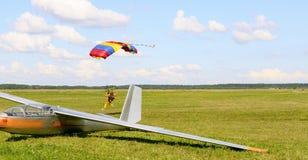 Skydiver landing near glider. Stock Image
