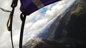 Skydiver open parachute above mountains covered by greenery. Extreme sport. stock footage