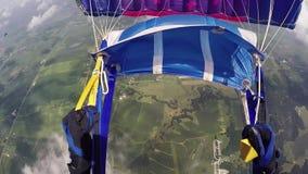 Skydiver opent valscherm in hemel boven groene gebieden extreem adrenaline Wolken stock footage