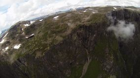 Skydiver parachuting above mountains covered by greenery and snow. Extreme sport stock footage