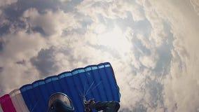 Skydiver profesional en casco que se lanza en paracaídas en cielo nublado altura Deporte velocidad almacen de metraje de vídeo