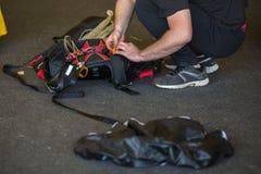 Skydiver que dobra-se acima de seu paraquedas preto na terra Fotografia de Stock