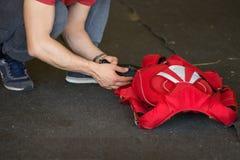 Skydiver que dobra-se acima de seu paraquedas vermelho na terra Imagem de Stock Royalty Free