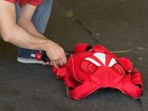 Skydiver que dobra-se acima de seu paraquedas vermelho na terra Imagens de Stock