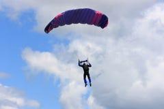 Skydiver que salta de paraquedas para baixo à terra. Imagens de Stock