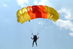 Skydiver que salta en caída libre con el paracaídas rojo amarillo-naranja colorido en la taza que se lanza en paracaídas del ` s  Imagen de archivo