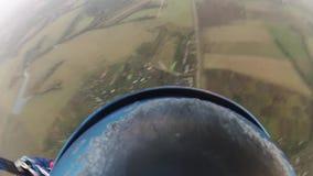Skydiver que se lanza en paracaídas en cielo sobre campos verdes Actividad extrema adrenalina almacen de metraje de vídeo