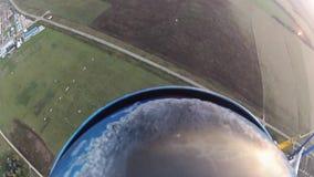 Skydiver que se lanza en paracaídas en cielo sobre campos verdes Actividad extrema adrenalina metrajes