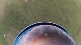Skydiver que se lanza en paracaídas en cielo sobre campos verdes Actividad extrema aterrizaje almacen de video