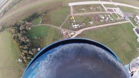 Skydiver que se lanza en paracaídas en cielo sobre campos verdes Manía extrema adrenalina almacen de video