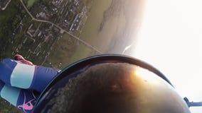Skydiver que se lanza en paracaídas en cielo sobre tierra verde Actividad extrema adrenalina metrajes