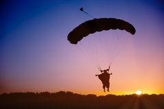 Skydiver silhouette under parachute. Canopy in wingsuit against sunset sky Stock Images