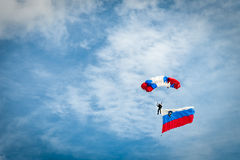 Skydiver with Slovenian flag and parachute in colors of Slovenia. Skydiver with Slovenian flag, parachute in colors of Slovenian flag Royalty Free Stock Photography