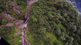 Skydiver som hoppa fallskärm ovanför berg som täckas av gröna träd extremt Landskap stock video