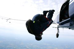 Skydiver tumbles out of an airplane Royalty Free Stock Image
