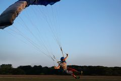 Skydiver under a dark blue and grey little canopy of a parachute stock image
