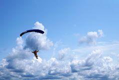 Skydiver under a dark blue little canopy of a parachute on the b royalty free stock photo