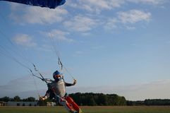 Skydiver under a dark blue little canopy of a parachute is landing on airfield, close-up royalty free stock photos